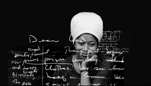 Artistic B&W photo of Alice Walker wearing a white turban, with abstract writing over the top